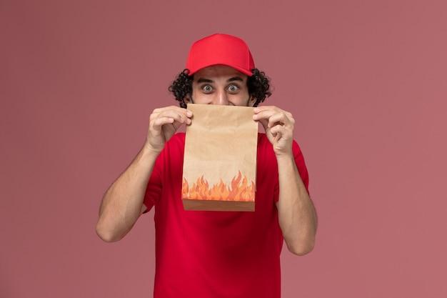 Uomo di consegna maschio del corriere di vista frontale in camicia rossa e mantello che tiene il pacchetto di cibo di carta sul dipendente dell'azienda di consegna di lavoro di servizio della parete rosa