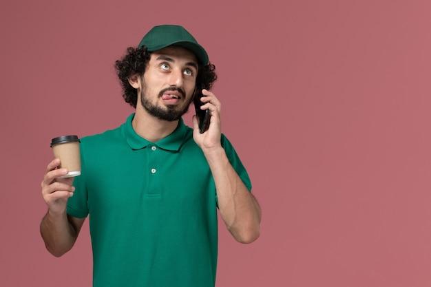 Corriere maschio vista frontale in uniforme verde e mantello che tiene tazza di caffè e parlando al telefono sul servizio di consegna uniforme sfondo rosa