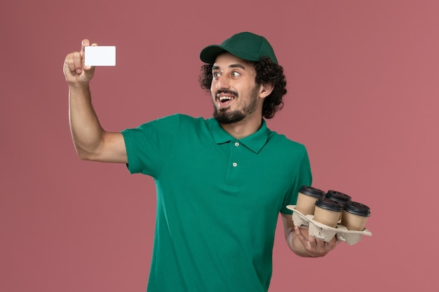 Front view male courier in green uniform and cape holding coffee cups with card on the pink background service uniform delivery job