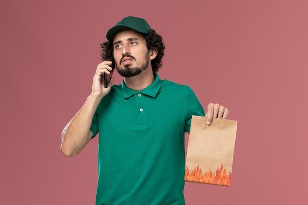 Corriere maschio di vista frontale in uniforme verde e mantello che tiene il pacchetto di cibo e parla al telefono sul lavoro maschile di consegna uniforme di servizio sfondo rosa