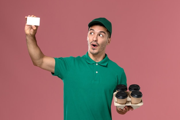 Front view male courier in green uniform holding brown coffee cups and card on light-pink background
