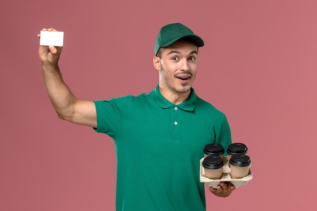 Front view male courier in green uniform holding brown coffee cups and card on pink background  male