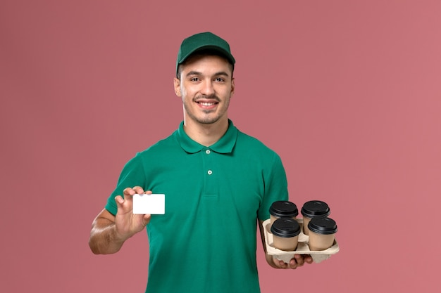 Front view male courier in green uniform holding brown coffee cups and card on pink background
