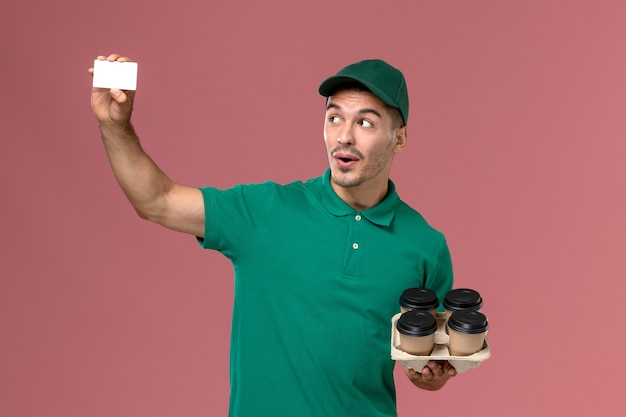 Front view male courier in green uniform holding brown coffee cups and card on the pink