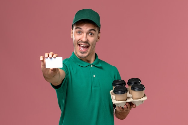 Front view male courier in green uniform holding brown coffee cups and card rejoicing on pink background