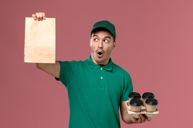 Front view male courier in green uniform holding brown coffee cups and food package on pink background