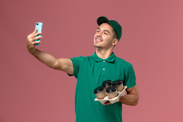 Front view male courier in green uniform holding brown coffee cups taking selfie on pink background