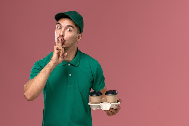 Front view male courier in green uniform holding brown delivery coffee cups asking to be silent on pink desk