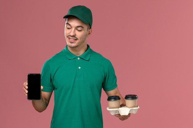 Front view male courier in green uniform holding brown delivery coffee cups and phone on the pink desk