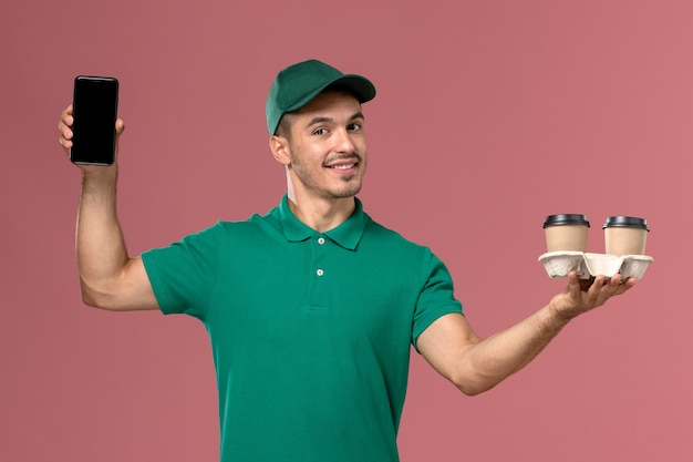 Front view male courier in green uniform holding brown delivery coffee cups and phone with smile on pink desk