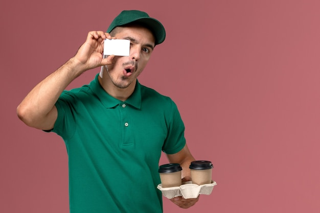 Front view male courier in green uniform holding brown delivery coffee cups and white plastic card on pink desk