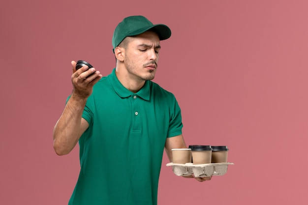 Front view male courier in green uniform holding delivery coffee cups smelling on the pink background