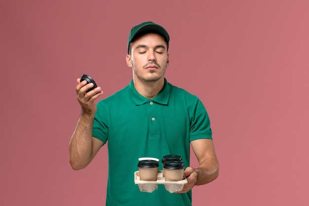 Front view male courier in green uniform holding delivery coffee cups smelling their scent on pink desk