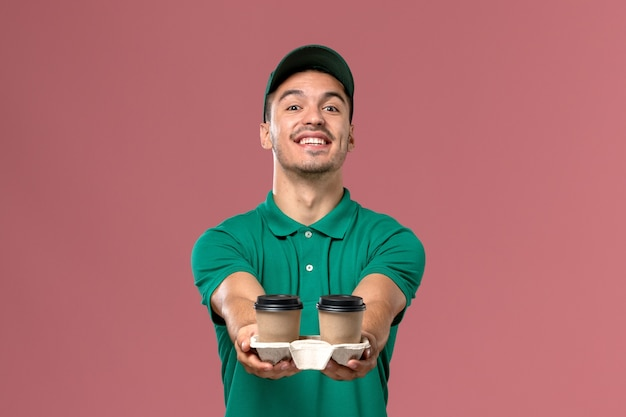 Front view male courier in green uniform holding delivery coffee cups and smiling on pink background