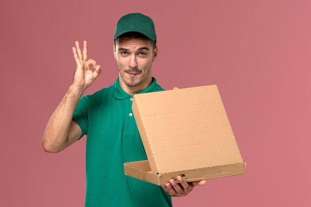 Front view male courier in green uniform holding food box and opening it on light pink background