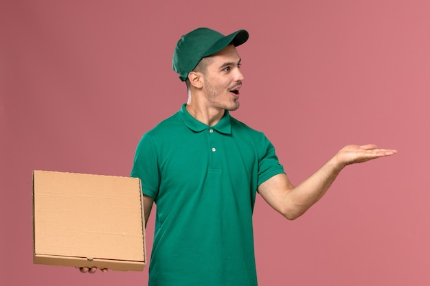 Front view male courier in green uniform holding food box on the pink background