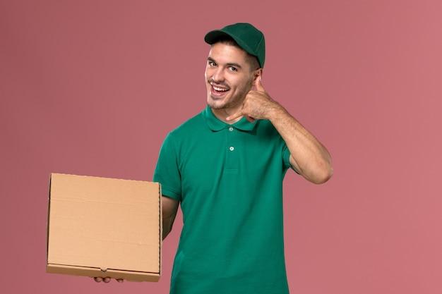 Corriere maschio di vista frontale in scatola di cibo della tenuta uniforme verde e posa di telefonata che mostra su fondo rosa
