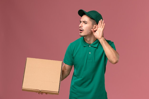 Front view male courier in green uniform holding food box trying to hear out on pink background