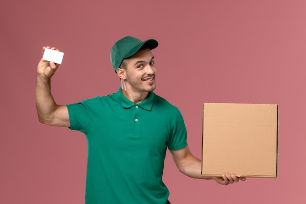 Front view male courier in green uniform holding food box with white card on pink desk