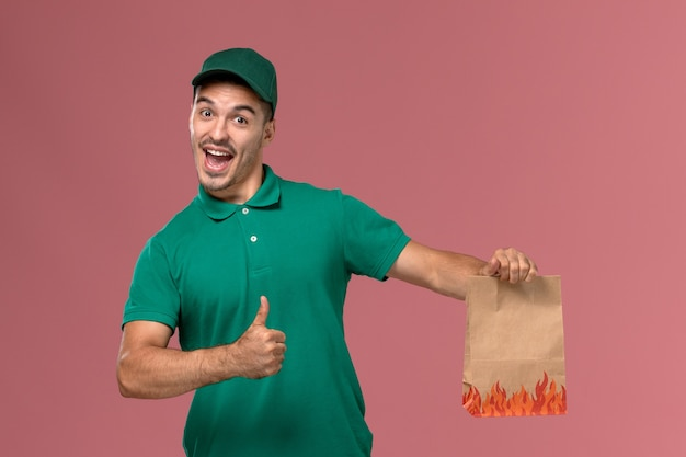 Front view male courier in green uniform holding food package and rejoicing on light-pink background