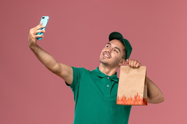 Front view male courier in green uniform holding food package and taking photo with it on pink background