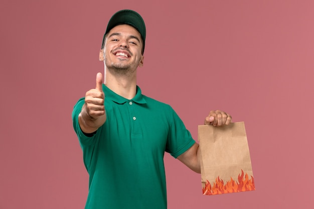 Front view male courier in green uniform holding paper food package smiling on light-pink background