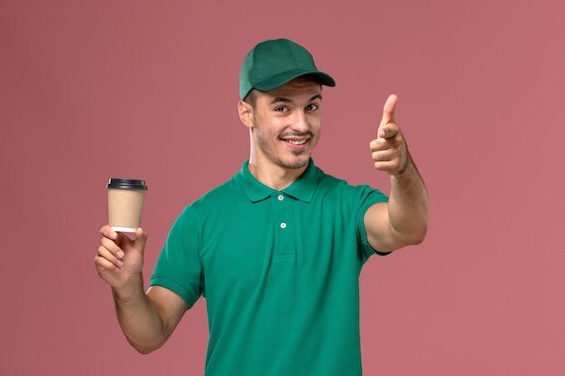 Corriere maschio di vista frontale in uniforme verde che sorride e che tiene la tazza di caffè sui precedenti rosa