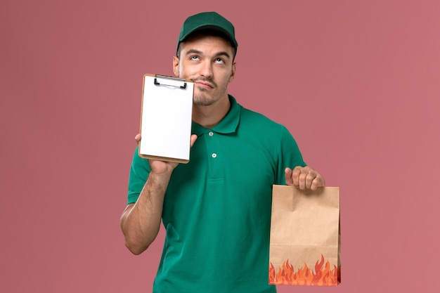 Corriere maschio di vista frontale in uniforme verde che pensa e che tiene il pacchetto dell'alimento con il blocco note su fondo rosa-chiaro