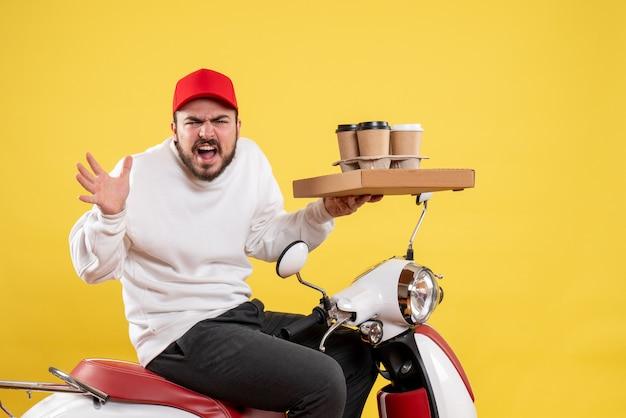 Vista frontale del corriere maschio che tiene consegna caffè e cibo sulla parete gialla