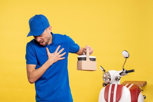 Вид спереди мужской курьер, держащий доставку кофе с душевной болью на желтой рабочей униформе, работа, служба, работа на велосипеде