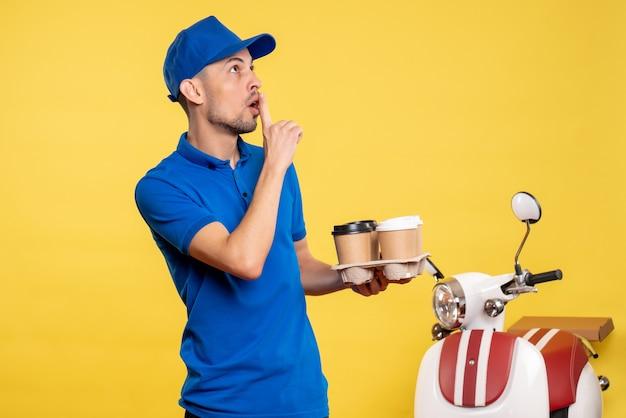 Вид спереди мужской курьер, держащий доставку кофе на желтом цвете, работник службы, работа, эмоция, униформа, велосипед