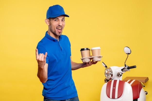 Вид спереди мужской курьер, держащий доставку кофе на желтом цвете, рабочий сервисный велосипед, рабочая эмоция, униформа