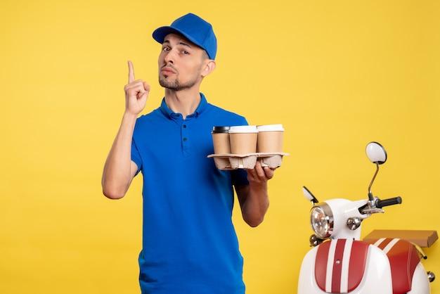 Вид спереди мужской курьер, держащий доставку кофе на желтом цвете, работник службы доставки, единообразный велосипед