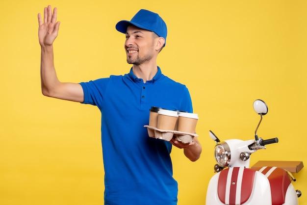 Вид спереди мужской курьер, держащий доставку кофе на желтом цвете, работник службы, работа, доставка эмоций, униформа, велосипед