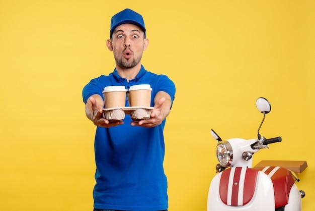 Вид спереди мужской курьер, держащий доставку кофе на желтом цвете, работник службы, работа, эмоции, доставка, униформа, велосипед
