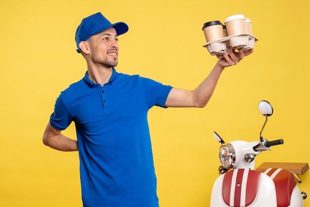 黄色の労働者サービス仕事仕事配達制服自転車で配達コーヒーを保持している正面図男性宅配便