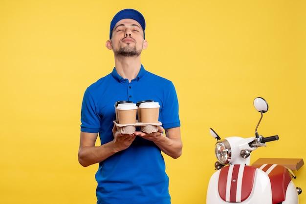 Вид спереди мужской курьер, держащий доставку кофе на желтом цвете, рабочий, доставка, униформа, велосипедная работа