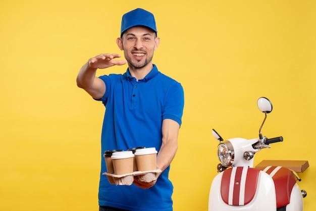 Вид спереди мужской курьер, держащий доставку кофе на желтом цвете, сервис эмоций на велосипеде