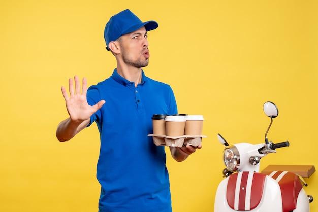 Corriere maschio vista frontale che tiene il caffè di consegna sulla bici uniforme di consegna del lavoro di emozione del lavoro di colore giallo