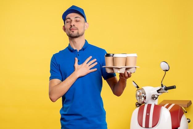Corriere maschio di vista frontale che tiene il caffè di consegna sul lavoro uniforme della bici di consegna di servizio dell'operaio di colore giallo