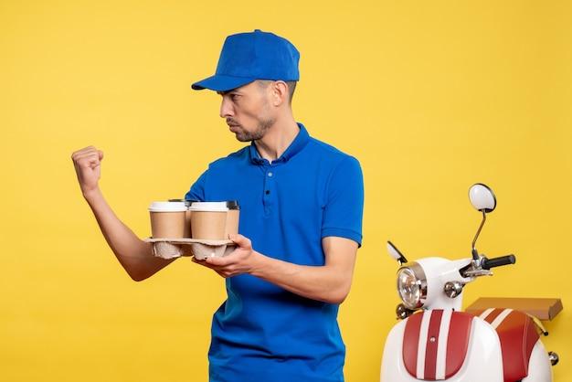 Corriere maschio di vista frontale che tiene il caffè di consegna sulla bici uniforme di consegna di lavoro di emozione di servizio dell'operaio di colore giallo
