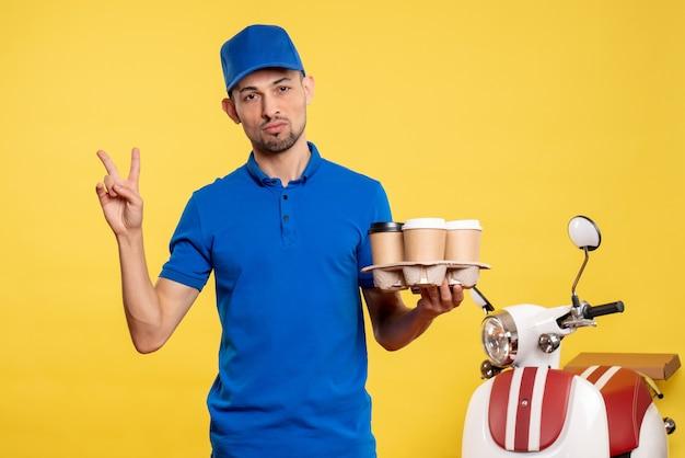 Corriere maschio di vista frontale che tiene il caffè di consegna sul lavoro della bici di consegna del lavoro di servizio dell'operaio di colore giallo