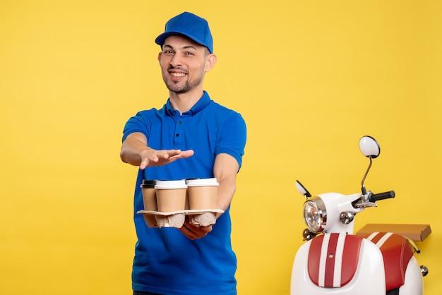 Corriere maschio di vista frontale che tiene il caffè di consegna sulla bici uniforme di consegna di lavoro di emozione del lavoro di servizio dell'operaio di colore giallo