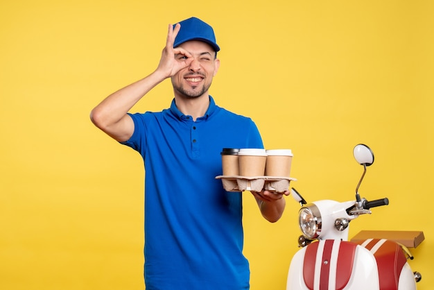 Front view male courier holding delivery coffee on yellow color worker service work emotion job delivery uniform
