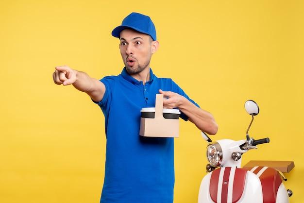 Corriere maschio di vista frontale che tiene il caffè di consegna sul lavoro uniforme della bici di servizio di lavoro di lavoro di colore giallo dell'operaio