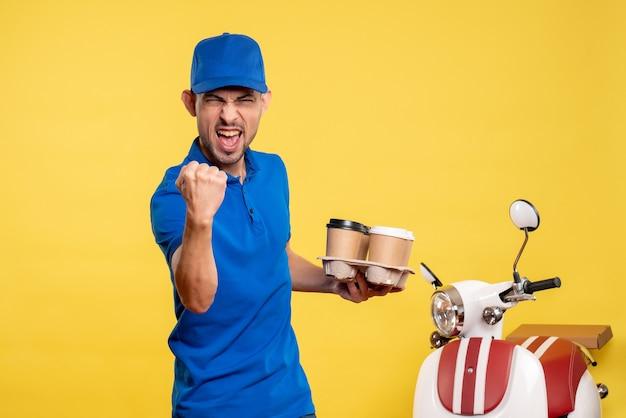Corriere maschio di vista frontale che tiene il caffè di consegna sulla bici uniforme di consegna del lavoro di emozione del lavoro dell'operaio di colore giallo