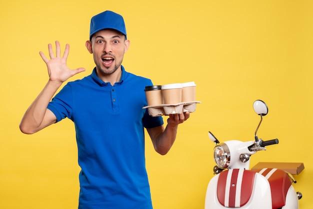 Corriere maschio di vista frontale che tiene il caffè di consegna sul lavoratore della bici dell'uniforme di consegna di servizio di colore di lavoro giallo