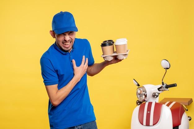 Corriere maschio di vista frontale che tiene il caffè di consegna sul lavoratore della bici uniforme di consegna del lavoro di servizio di colore di lavoro giallo Foto Gratuite