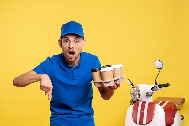 Front view male courier holding delivery coffee on yellow job color work delivery uniform bike worker