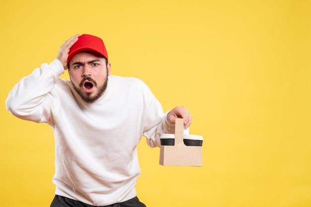 Vista frontale del corriere maschio che tiene il caffè di consegna sulla parete gialla